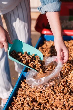 Person lays nuts in a transparent bag. food market. Natural products. vegetarianism. Vegan food