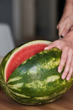 Hands holding a watermelon. The watermelon was cut and separated. Watermelon is red, green and wet. Watermelon looks delicious.