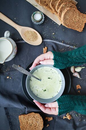 female hands in a sweater hold a plate with soup in their hands. Winter food concept. Home comfort.