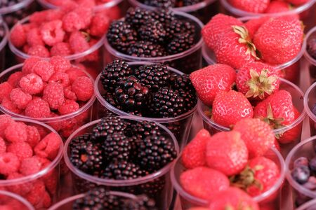 Food market. A counter with plastic containers and glasses filled with fresh berries. Blackberry, Strawberry, Blueberry, Raspberry