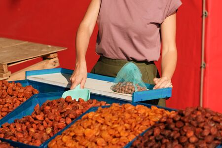 Dried fruit seller. young woman imposes dried apricots and weighs it for the buyer.super food Фото со стока