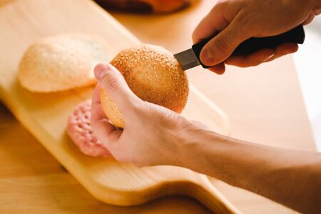Preparation of burger. Cooking hamburger concept. Cook preparing burger adding meet. Cook cuts burger bun. Juicy american burger with beef cutlet. Tasty grilled home made burgers cooking Stock Photo