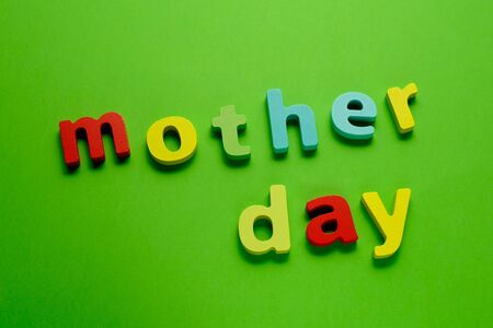 Word MOTHER DAY made of color wooden letter, isolated on green background. Learning the English alphabet and the English language. The concept of child education, school, kindergarten,preschool education