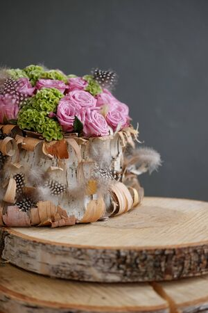 Beautiful spring bouquet closeup with pink roses and green carnations, decorated with feathers and birch bark on a background of a gray wall. Bridal bouquet. Mother's Day, International Women's Day