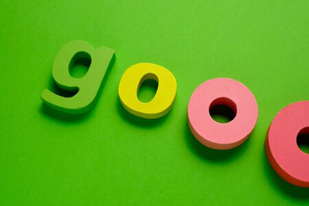 Word GOO made of color wooden letter, isolated on green background. Learning the English alphabet and the English language. The concept of child education, school, kindergarten,preschool education
