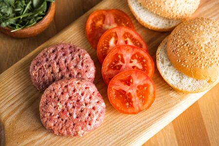 Buns, raw beef cutlets, tomatoes and herbs for burgers cooking. Concept of american fast food. Juicy american burger with beef cutlet. Tasty grilled home made burgers cooking Stock Photo