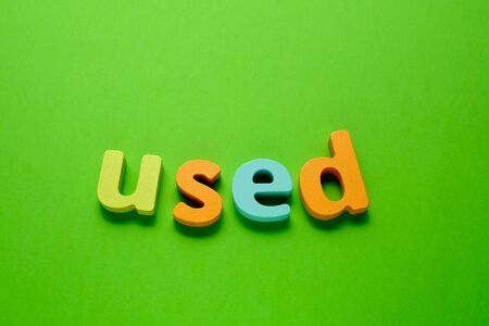 Word USED made of color wooden letter, isolated on green background. Learning the English alphabet and the English language. The concept of child education, school, kindergarten,preschool education