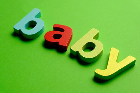 Word BABY made of color wooden letter, isolated on green background. Learning the English alphabet and the English language. The concept of child education, school, kindergarten,preschool education