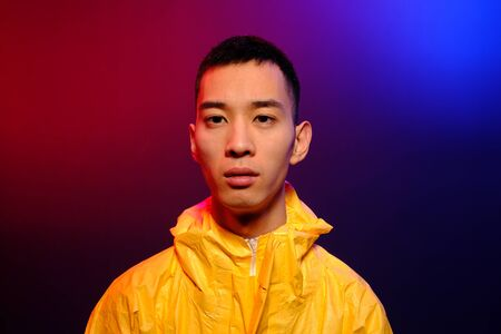 Asian man in a yellow suit of chemical protection on a colored trendy background. Fashion shooting in Asian style, neon lights and fashionable clothes, professional model. Coronavirus Protection.