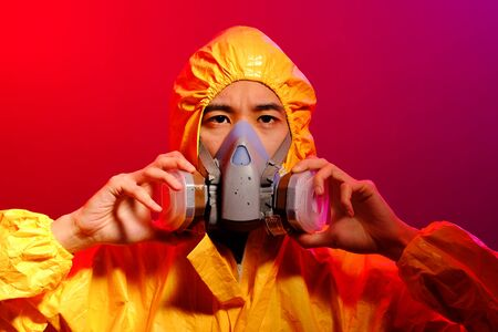 Asian man in a yellow suit of chemical protection and in a protective mask on a colored trendy background.