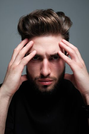 A young dark-haired man with a beard holds his head and shows different human emotions: hatred, fear, despair, horror, malaise, headache, clairvoyance. Close-up studio portrait of a man.