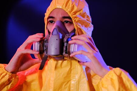 Asian man in a yellow suit of chemical protection and in a protective mask on a colored trendy background. Concept Breaking Bad.