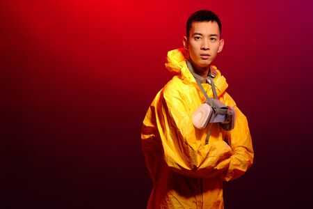 Asian man in a yellow suit of chemical protection and in a protective mask on a colored trendy background. Concept Breaking Bad. The concept of the spread Epidemic of the coronavirus Reklamní fotografie