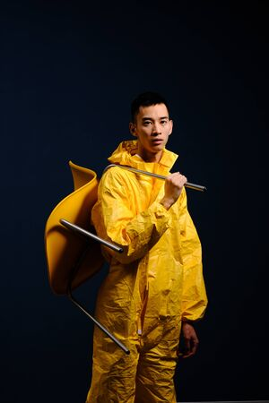 Asian man in a yellow chemical protection suit posing with a yellow plastic chair on a colored trendy background. Fashion shooting in Asian style, night city, neon lights and fashionable clothes Reklamní fotografie