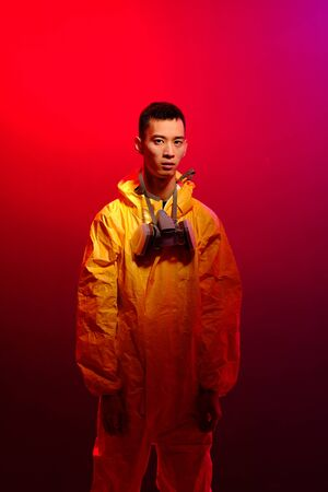 Asian man in a yellow suit of chemical protection and in a protective mask on a colored trendy background. Concept Breaking Bad. The concept of the spread Epidemic of the coronavirus