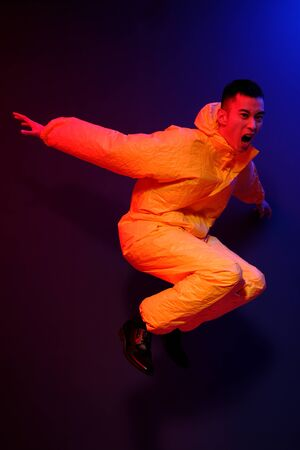An Asian man in a yellow chemical protection suit screams in a jump on a colored trend background. Conceptual fashion shooting in Asian style. Coronavirus Protection Reklamní fotografie