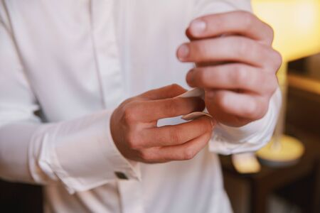 Grooms morning preparation.Handsome man getting dressed and preparing for the wedding.Friend helping groom getting ready in the room for wed day. Stock Photo