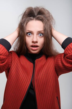 Portrait of a young funny girl with blue eyes and brown hair in a black T-shirt and a red bomber jacket. The girl holds on to her hair and fools around, has fun, grimaces, shows human emotions