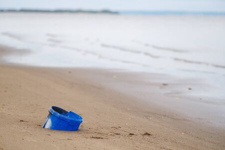 Blue plastic bucket in the sand on the beach. Pollution of the environment and the oceans. Microplastic in the ocean. Pollution and recycling concept