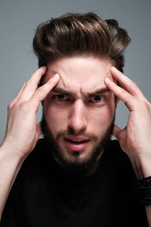 A young dark-haired man with a beard holds his head and shows different human emotions: hatred, fear, despair, horror, malaise, headache, clairvoyance. Close-up studio portrait of a man. Banque d'images