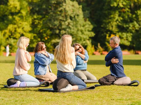 A group of young people meditate outdoors in a park. Meditation and yoga, healthy lifestyle concept. Spiritual Restoration. Wellbeing, wellness concept