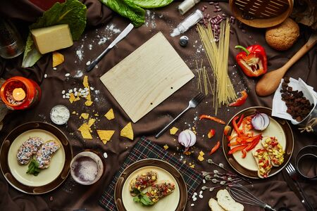 Traditional italian food on a dark background, flat lay. Various ingredients for italian food. Bruschetta, pasta, tomatoes, peppers, cheese, etc.