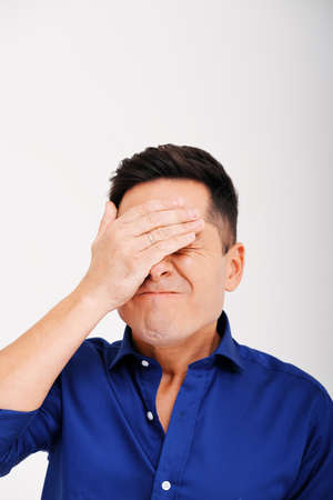 Studio portrait of young man who closes his eyes with his hands against plain background. Human emotions