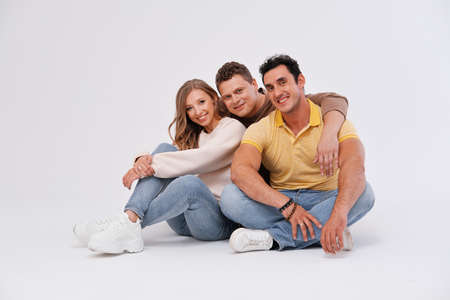 Three friends are sitting on the floor, hugging and smiling on a light background. Friendship concept. Фото со стока