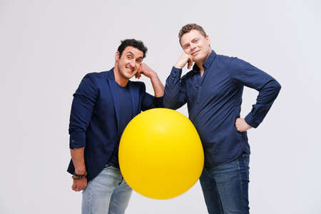 Studio portrait of two men posing with big yellow ball against plain background