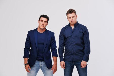 Studio portrait of two male friends against plain background. Friendship man concept. Фото со стока