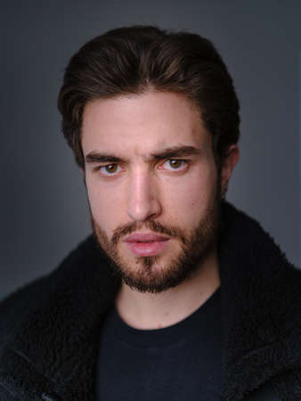 A large portrait of a stylish young man with a beard and dark hair in a black leather jacket with faux fur collar.