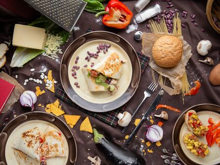 pepper corn black bean quinoa burritos. flat lay, shot from above on a black background. Mexican food mix colorful background Mexico Banco de Imagens