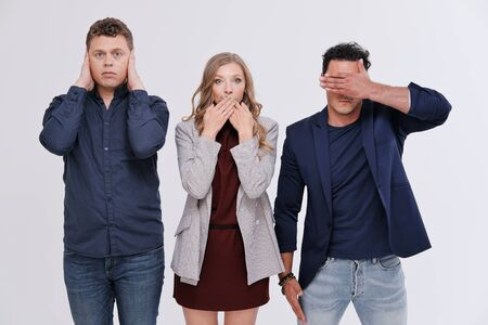 Studio portrait of three friends against plain background. Three friends show the concept: I see nothing, I hear nothing, I will not tell anyone