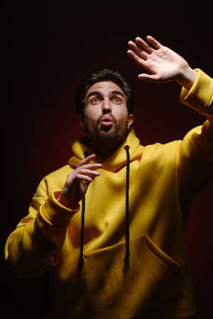 A young man of 25-30 years old in a yellow sweatshirt emotionally pulls his hands up on red wall background. The concept of modern fashion photography. Brutal man portrait Reklamní fotografie
