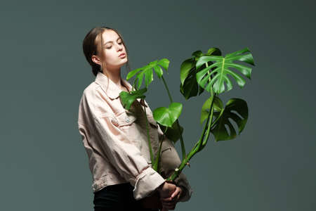 Portrait of a young beautiful girl 20-25 years old with green eyes and long hair. A girl in a pink jacket in black jeans holds in her hands a monstera flower in a pot posing on a gray background. 免版税图像