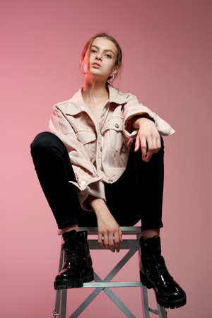 Portrait of a young beautiful girl 20-25 years old with green eyes and long hair. A girl in a pink jeans in black jeans sits on a white wooden bar stool and poses on a pink background. 免版税图像