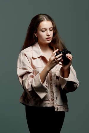 Portrait of a young beautiful girl 20-25 years old with green eyes and long hair. A girl photographer in a pink jacket holds a mirrorless camera in her hands.