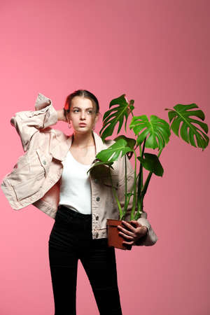 Portrait of a young beautiful girl 20-25 years old with green eyes and long hair. A girl in a pink jacket in black jeans holds in her hands a monstera flower in a pot posing on a pink background.