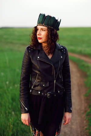 Close-up portrait of a young woman of 25-30 years old with curly red hair, in a black leather jacket and a tiara with feathers. Portrait of a woman on a background of green grass