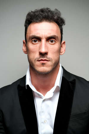 Close up portrait of a man 30-34 years old in a white shirt and a black jacket on a gray background. A man with curly hair, big eyes and bristles shows different human emotions.