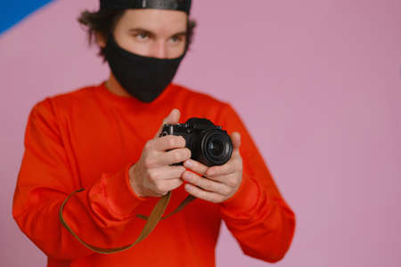 A young man of 25-30 years old in a black protective mask and in a red sweatshirt holds a mirrorless camera in his hands. Male photographer uses a mirrorless camera to take a picture. Banco de Imagens