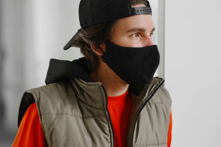 A young man of 25-30 years old in a black protective mask, a cap and a red jacket posing on a gray background. Coronavirus protection.