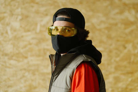 A young man of 25-30 years old in a black protective mask, yellow goggles, a cap and a red jacket posing on a gray background. Coronavirus protection. Фото со стока