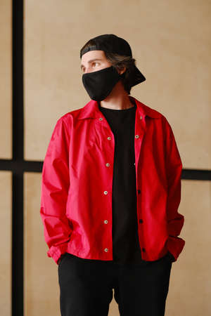 Portrait of a young man 25-30 years old in a black protective mask, black cap and red jacket. Young fashionable man posing over bright background. Fashion photography concept