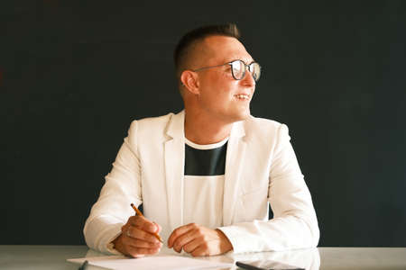 A young school teacher a man in a white jacket and glasses checks the homework of his students and prepare for a new lesson. Education, school, college and university concept. Фото со стока