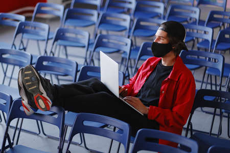 Portrait of a man 25-30 years old in a black protective mask, cap and red jacket. A man sits alone in a large room with many empty blue chairs and works on his laptop. Freelance and lockdown concept Фото со стока