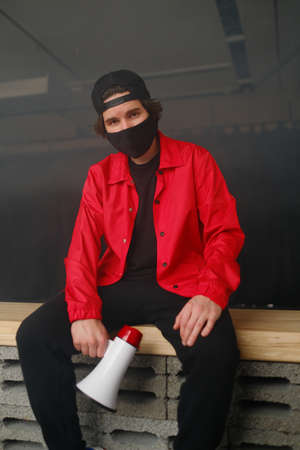 Emotional young man 25-30 years old in a black protective mask, a cap and a red jacket holding a megaphone against a dark background. Protest concept