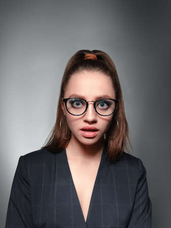 A young girl 20-25 years old in glasses, a jacket and with a tail in the image of a teacher poses on a gray background and shows different emotions.