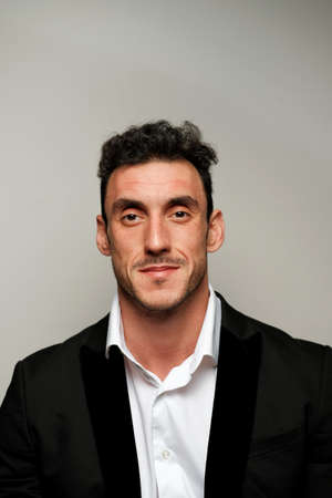 Close up portrait of a man 30-34 years old in a white shirt and a black jacket on a gray background. A man with curly hair, big eyes and bristles shows different human emotions. Фото со стока