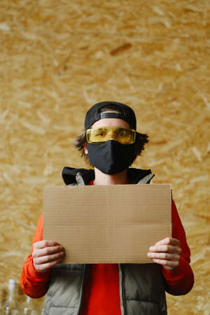A young man of 25-30 years old in a black protective mask, yellow glasses, a cap and a red jacket holds an empty cardboard sign in his hands. Protest concept. Blank mock up for design, mockup